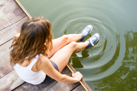 Young woman wearing jeans sneakers sitting in a river bank hanging her  legs over the water Stock Photo