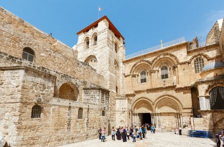 JERUSALEM, ISRAEL -  APRIL 06, 2016: Tourists and pigrims walk and sit on a square at the entrance to the Church of the Holy Sepulchre in Jerusalem on APRIL 06, 2016, Israel