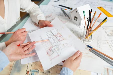 Binnenlandse ontwerpers die aan de tekeningen van de kleurenhand van een keukenbinnenland werken op het werkplaats. Foto van jonge ontwerpers werk concept