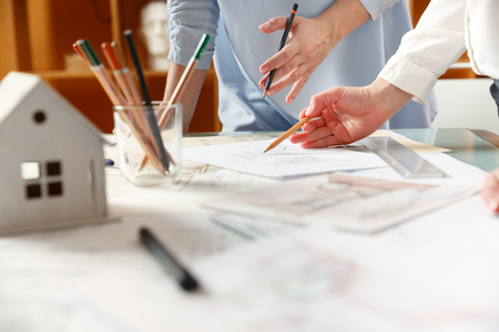 Interior designers working on hand drawings of  interior at work place. Photo of young designers work concept Stock Photo