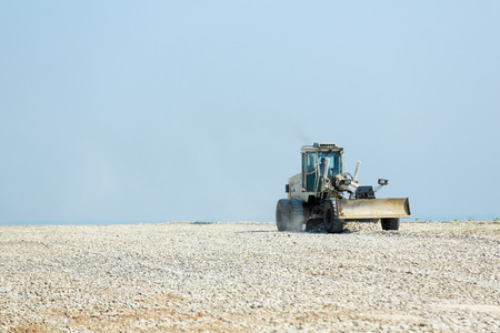 Industrial tractor grading surface prepearing it for further construction