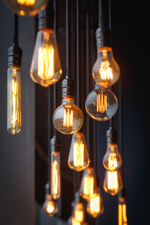 Vintage tungsten filament multiple lamps of different size and style hanging from the ceiling on a black wires as an interior design concept. Energy and design concept 写真素材