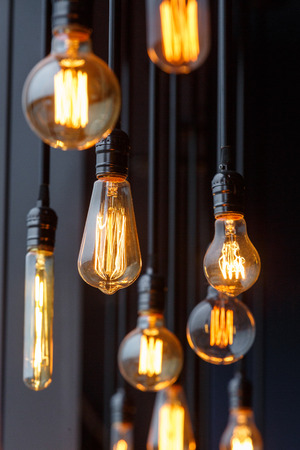 Vintage tungsten filament multiple lamps of different size and style hanging from the ceiling on a black wires as an interior design concept. Energy and design concept Imagens