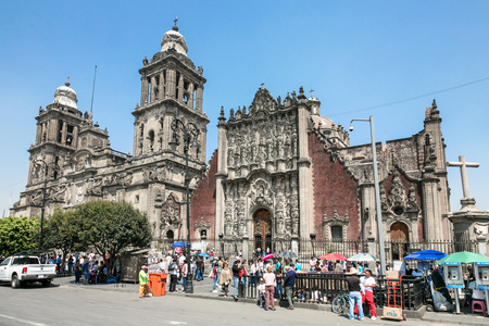 Mexico city, Mexico -MARCH 2012:   People crossing the street on Plaza de la Constitución or Zocalo in Mexico City on saturday in front of Cathedral Metropolitana  and Metropolitan Tabernacle . Редакционное