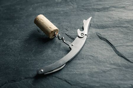 Stainless  wine corkscrew with a cork on a black rocky slate background