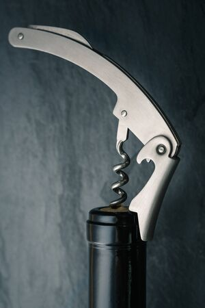 Stainless  wine corkscrew in a cork of wine bottle neck on a black rocky slate background
