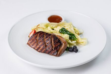 Grilled duck breast with vegatables and berry suase on a white plate. Restaurant serving Фото со стока