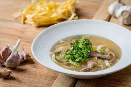 Fresh duck clear soup with noodles served in a white plate