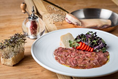 Fresh duck carpaccio served on a white plate with soft cheese