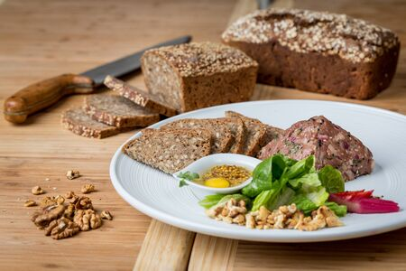Fresh tartar made from duck meat served on a white plate with bread,nuts and  mustard sauce Фото со стока