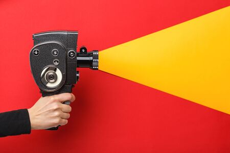 Female hand holding old style film movie camera imitating shooting process on a red background with yellow light coming through the lens Stock Photo
