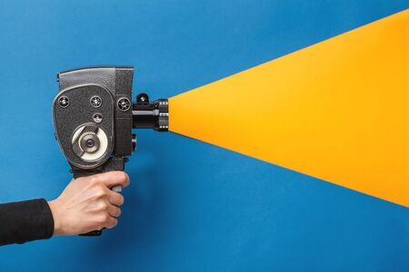 Female hand holding old style film movie camera imitating shooting process on a blue background with yellow light coming through the lens