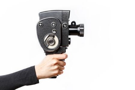 Female hand holding old style 8 mm movie camera isolated on a white background
