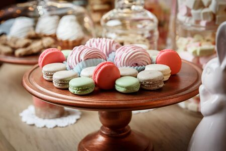 Macaroons and marshmellows on a wooden tray in cafe. Cake manufacturing Фото со стока