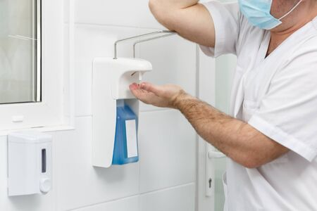 Doctor washing hands using disinfecting liquids in a surgical clinic. Healthcare and medicine concept