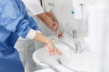 Doctors washing hands using disinfecting liquids in a surgical clinic. Healthcare and medicine concept Фото со стока