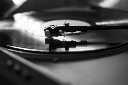 Closeup view of a tonearm and turntable playing vinyl record. Entertainment and music trends, black and white image
