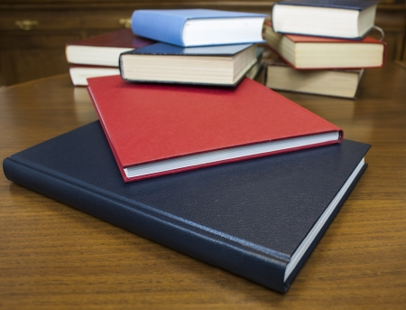 Many different sized colored and shaped books on wood table photo