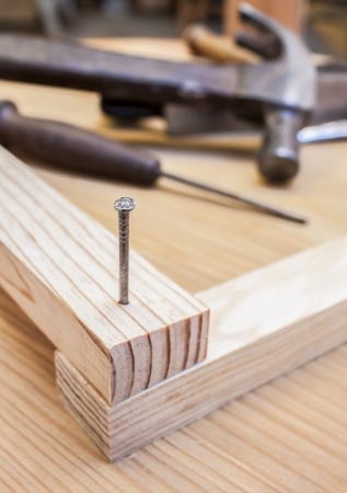 hammer and nail in wood table construction background photo
