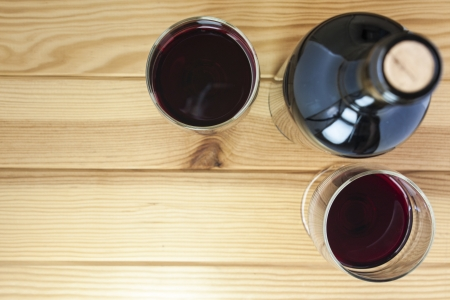 red wine on pine wood table background photo