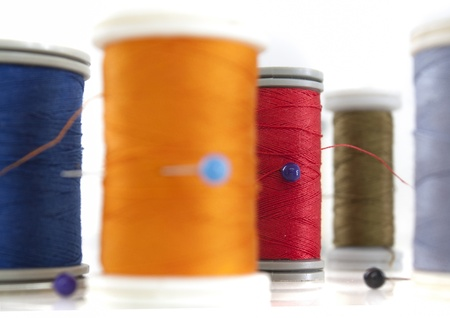 different thread reels on white background photo