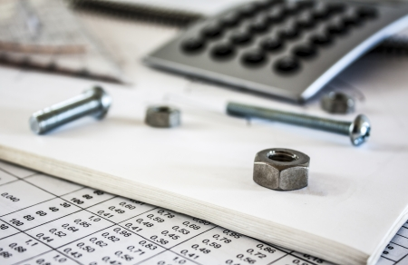 nuts screws  and calculator on technical drawing photo