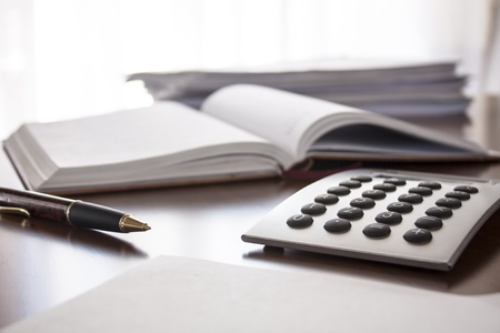 sitting at desk: planner with  pen and calculator on the table