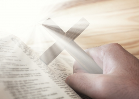 religious service: man holding the cross with bible and divine light Stock Photo