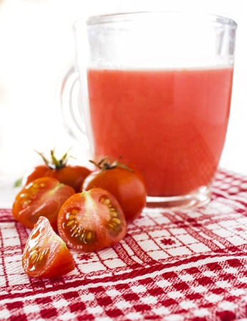 Drinking glass with tomato juice and ripe fresh tomato near  photo