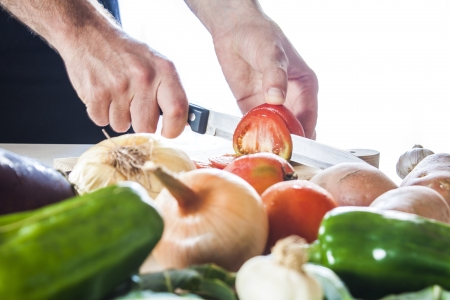 cutting tomatos with vegetables table Stock Photo