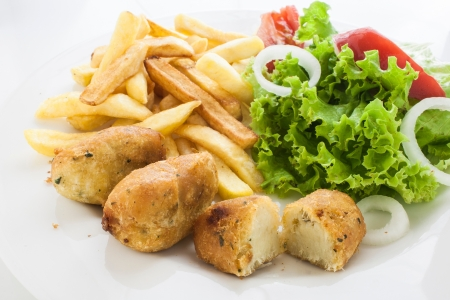 portuguese codfish cake with french fries and vegetables photo