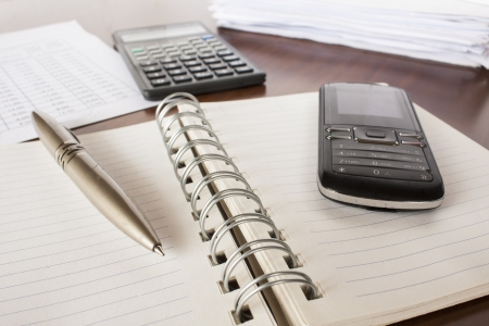 bills ,pen  cell phone,notebook and calculator,accounting