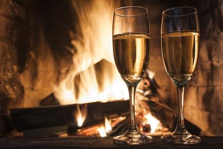 camino natale: bicchieri di champagne davanti al camino Archivio Fotografico