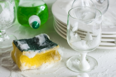 Washing glasses and plates with detergent and water Stockfoto