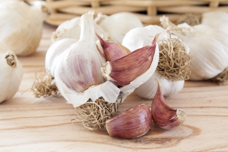 Garlic bulbs and cloves, over head view on pine wood table photo