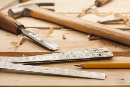carpenter items: carpenter tools,hammer,meter,chisel and shavings over wood table Stock Photo