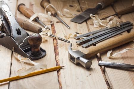 carpintero: Herramientas del carpintero, el martillo, el metro, el cincel y virutas sobre la mesa de madera