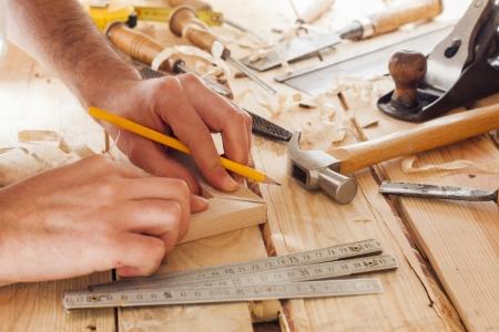 falegname: falegname di lavoro, martello, metro e cacciavite su sfondo di costruzione Archivio Fotografico