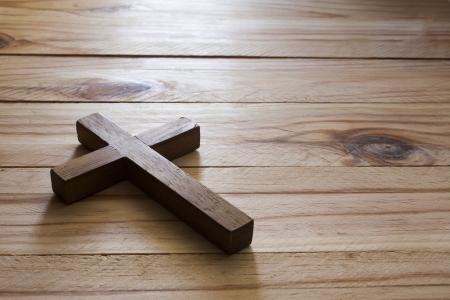 catholic symbols: Cross over  wood table with window light
