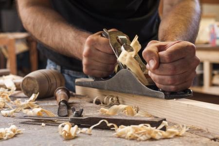 carpintero: carpintero que trabaja con el plano sobre fondo de madera Foto de archivo