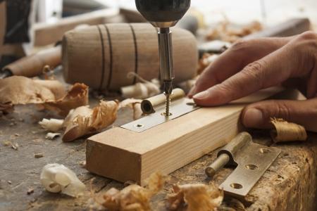 close-up van een timmerman geschroefd een scharnier op een houten plank Stockfoto