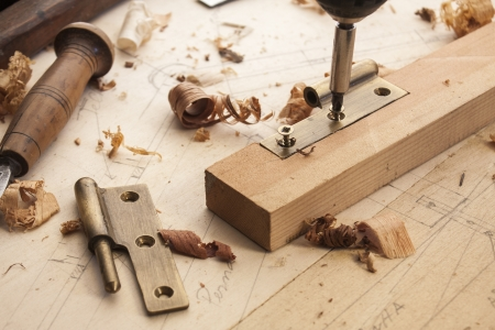 close up  of a carpenter screwed a hinge on a wooden plank Stock Photo