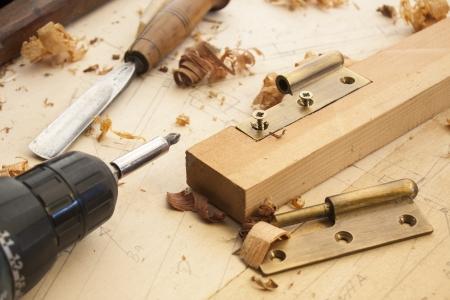 menuisier: pr�s d'un charpentier viss�e une charni�re sur une planche en bois Banque d'images