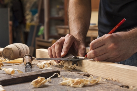 de hand van een timmerman nemen meting van een houten plank