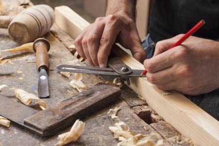 de hand van een timmerman die meting van een houten plank