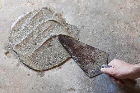 hand using trowel  with wet concrete floor