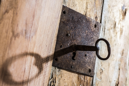 keyhole with key on a wooden antique door