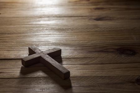 holy  symbol: Cruce mesa de madera con luz de ventana Foto de archivo