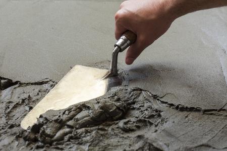 mortero: mano con llana con piso de concreto húmedo