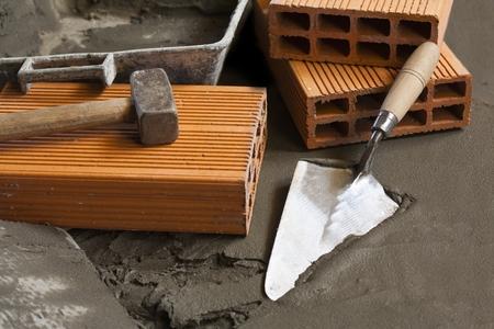 ladrillo: paleta y ladrillos con piso de hormigón húmedo Foto de archivo